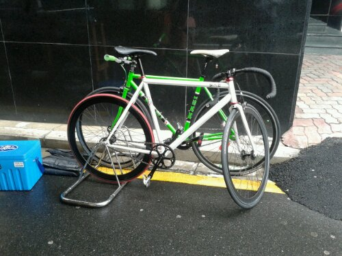 Two tidy fixie bicycles in the rain beside Tall Short Espresso in the Brisbane CBD